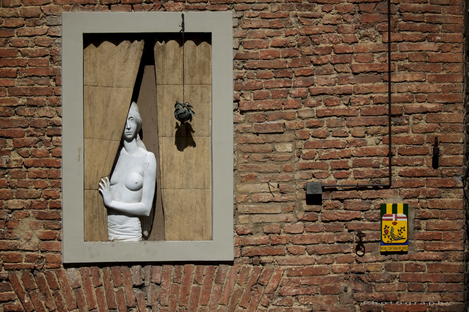 A marble woman at the window. Portrait or architecture?