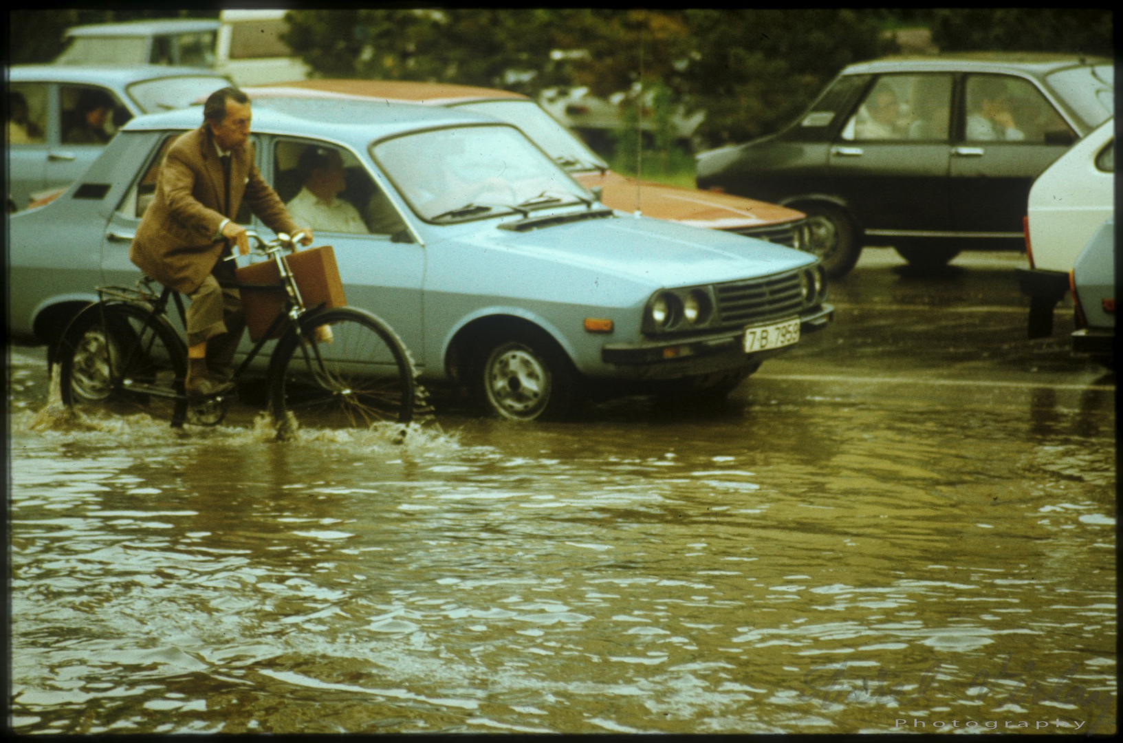 A man riding his bike to office on a dirty inundated street.