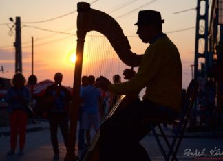 Street photo with a harp singer towards the end of another night.