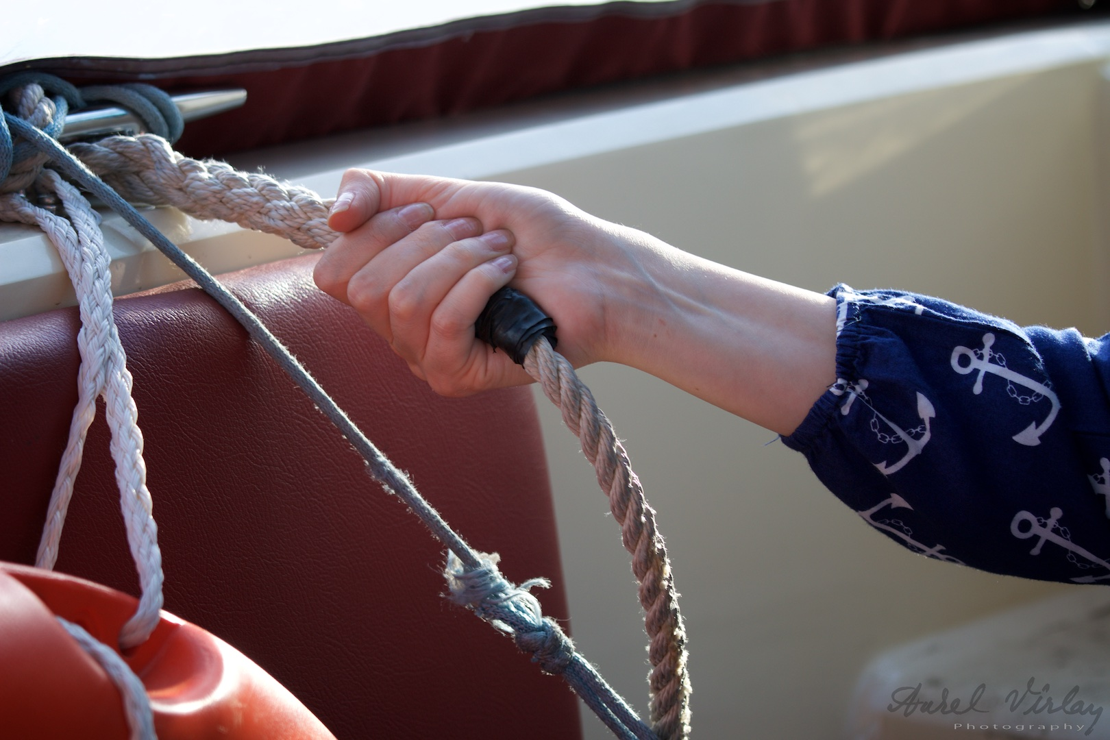 A delicate hand on the boat's rope. Details found photography