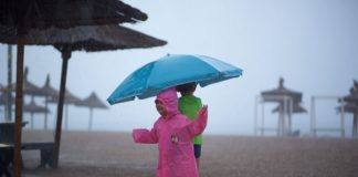 Who's happier? Is this pink girl in the summer rain or her photographer?