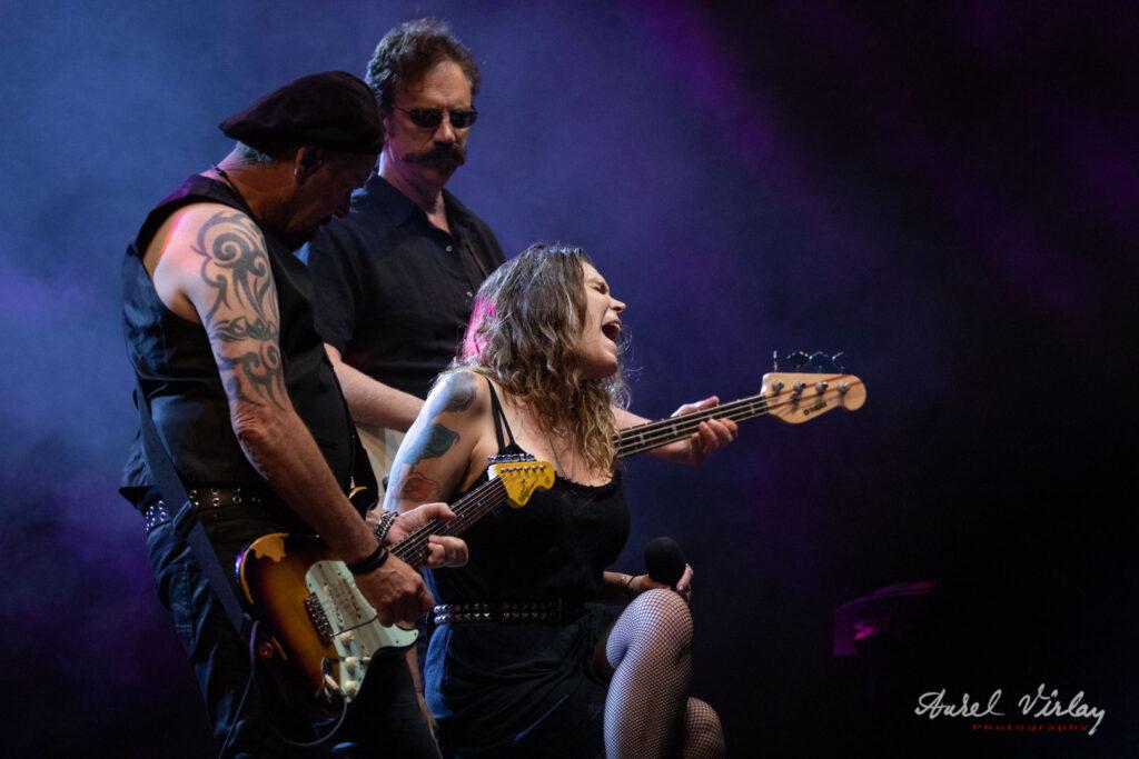 Beth Hart between guitarists on stage.